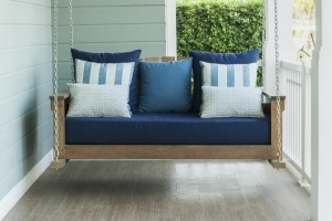 Refinished porch swing with blue pillows