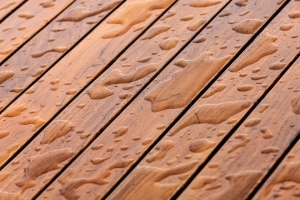 Water droplets beading on stained deck
