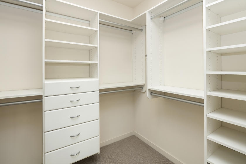 Built-in closet organizer with shelves, drawers, and rods