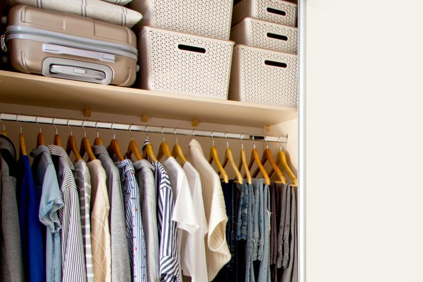 Organized closet with luggage and stacked plastic bins