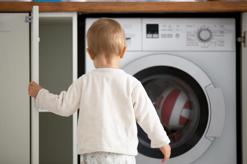 Little kid opening cabinet in laundry room