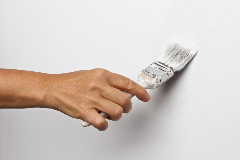 Touching up white wall with paint brush