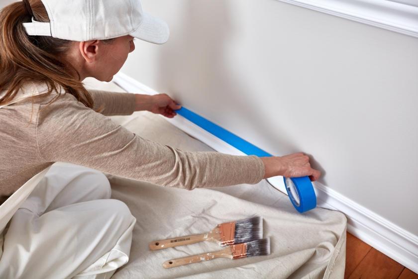 Woman laying painter's tape near baseboard